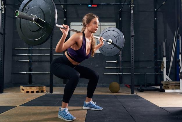 Femme, exécuter, épaule, squat, à, haltère