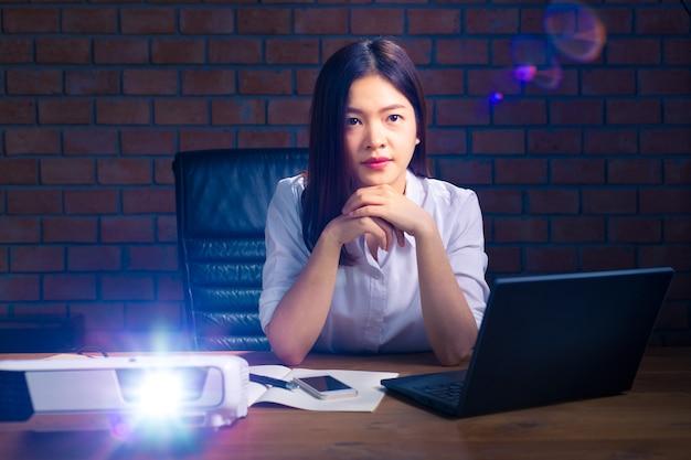 Femme exécutive asiatique regardant la projection projetée à l'écran
