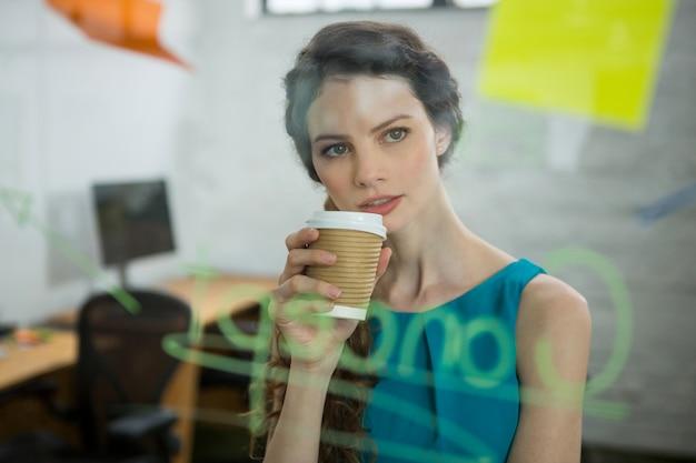 Femme exécutive réfléchie à la recherche de notes autocollantes tout en prenant un café