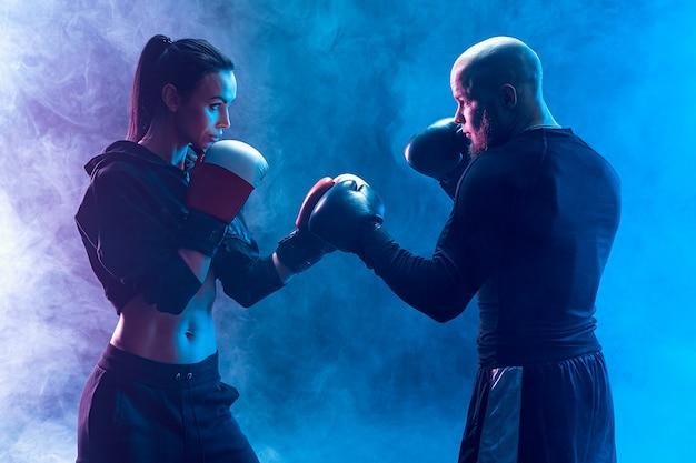 Femme exerçant avec entraîneur à la leçon de boxe et d'autodéfense