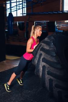 Femme exerçant avec un gros pneu