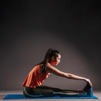 Femme exerçant sur un tapis d'étirement