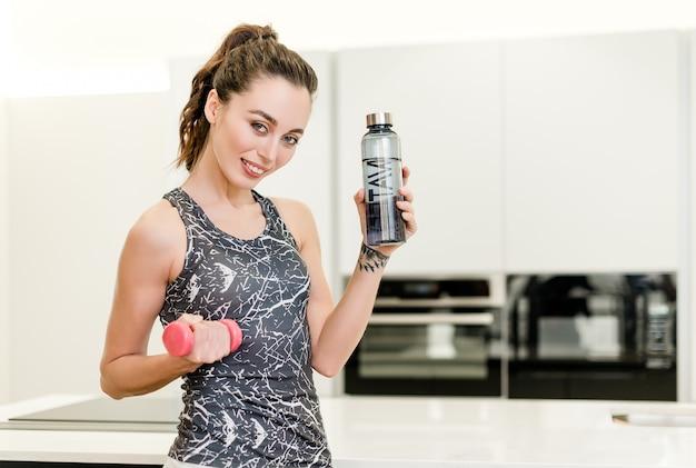 Femme exerce et travaille à la maison avec des haltères et une bouteille d'eau