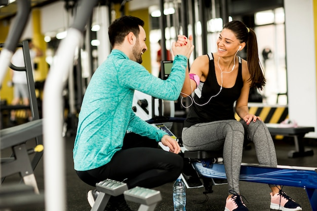 Femme exercice dans une salle de sport avec l'aide de son entraîneur personnel