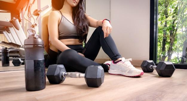 Femme exercice d'entraînement dans la salle de gym remise en forme se détendre après le sport d'entraînement avec haltère et bouteille d'eau.
