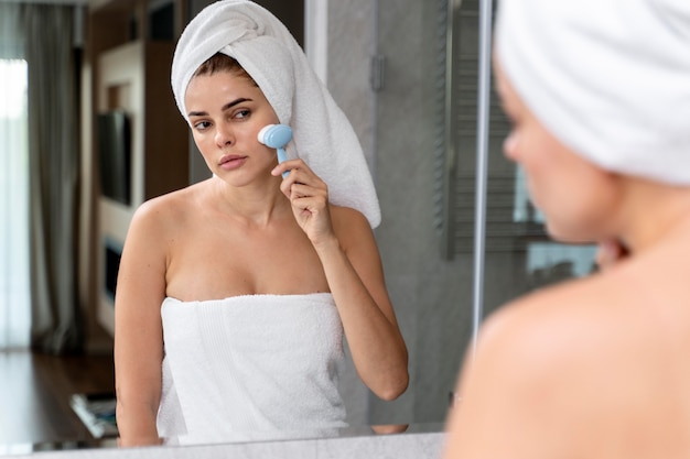 Femme exfoliant son visage avec une brosse