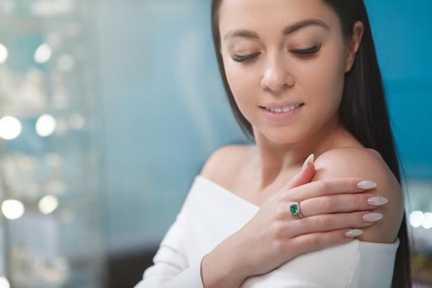 Femme exhibant une bague émeraude coûteuse sur son doigt
