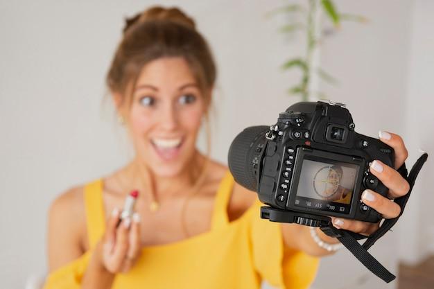 Femme exitée prenant des photos avec des produits de beauté