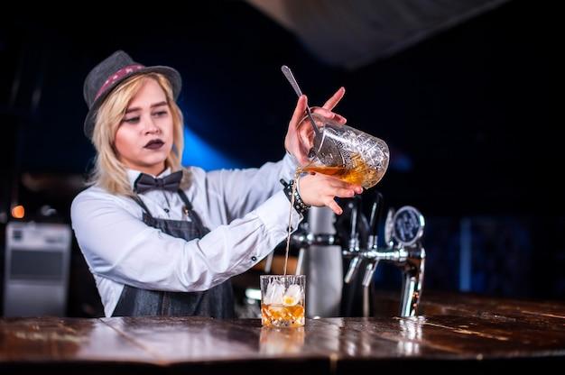 Femme expérimentée barman verser une boisson alcoolisée fraîche dans les verres de la boîte de nuit