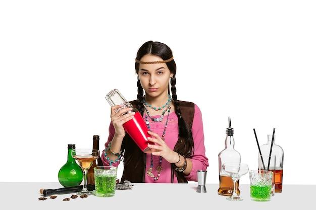 Une femme experte en barman prépare un cocktail au studio isolé sur un mur blanc