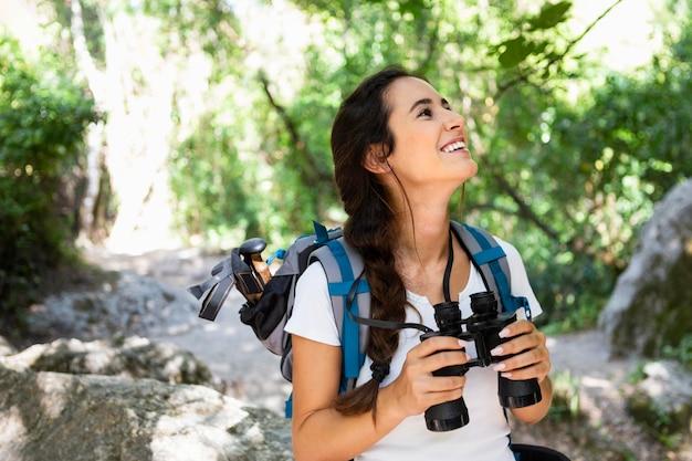Femme explorant et admirant la nature tout en utilisant des jumelles