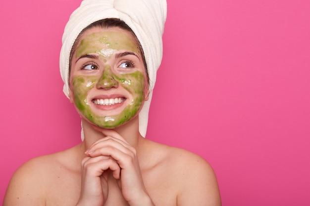 Femme avec une expression faciale rêveuse, a des procédures de spa quotidiennes, une peau fraîche et saine, regarde de côté