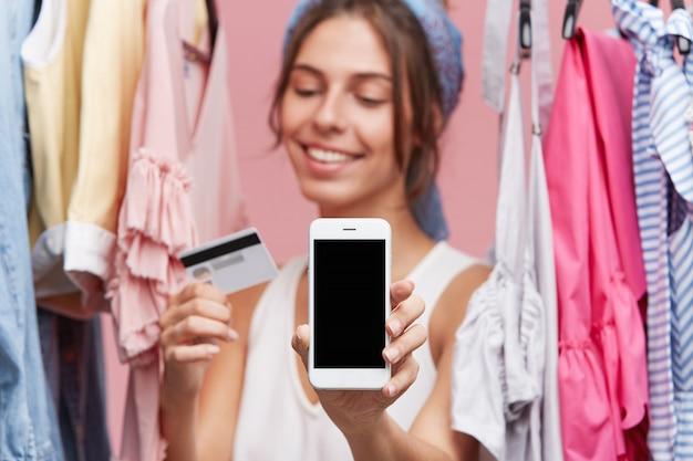 Femme avec une expression heureuse debout près du support avec des vêtements, gardant en mains une carte de crédit et un téléphone mobile moderne, étant heureuse d'acheter des vêtements en ligne. gens, achats en ligne