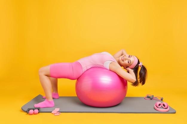 Femme avec une expression heureuse se penche sur une balle de fitness a une expression heureuse fait des exercices de pilates vêtue d'un body