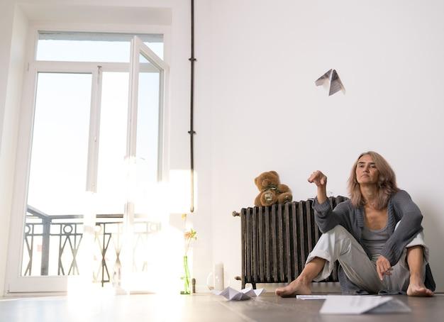 Une femme avec une expression indifférente a lancé un avion en papier dans son appartement