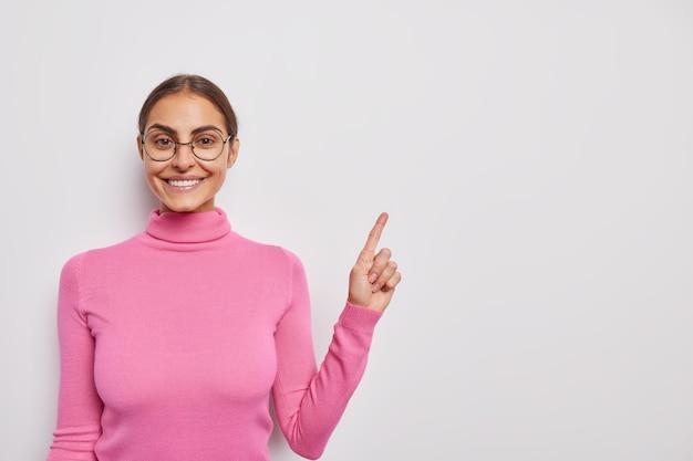 Une femme avec une expression joyeuse dit regardez ici indique dans le coin supérieur droit annonce votre texte pose sur blanc porte un col roulé rose et des lunettes rondes