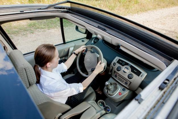 Femme avec une expression positive heureuse est assis sur le siège du conducteur