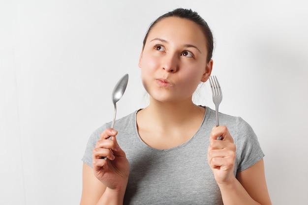 Femme avec une expression réfléchie tenant une fourchette et une cuillère