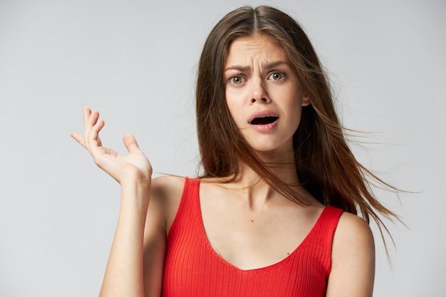 Une femme avec une expression surprise fait des gestes avec sa main bouche ouverte