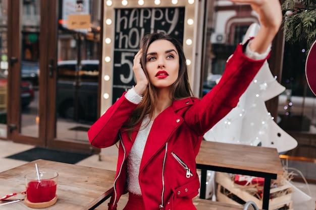 Femme avec une expression de visage grave en prenant une photo d'elle-même dans un restaurant de rue