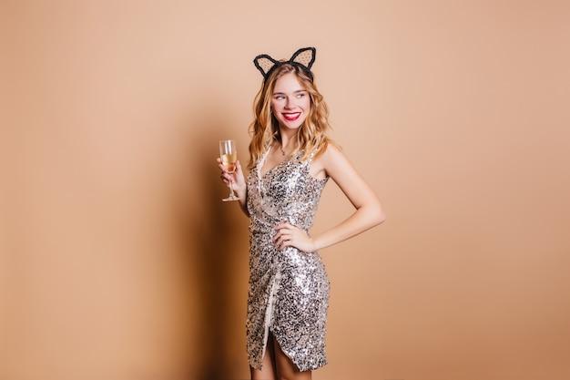 Femme extatique en accessoire de cheveux à la recherche de suite, boire du champagne sur un mur léger