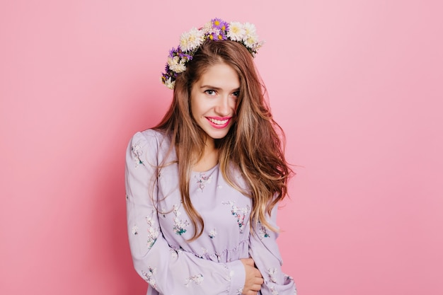 Femme extatique aux cheveux brun clair exprimant des émotions positives tout en posant dans une couronne de fleurs