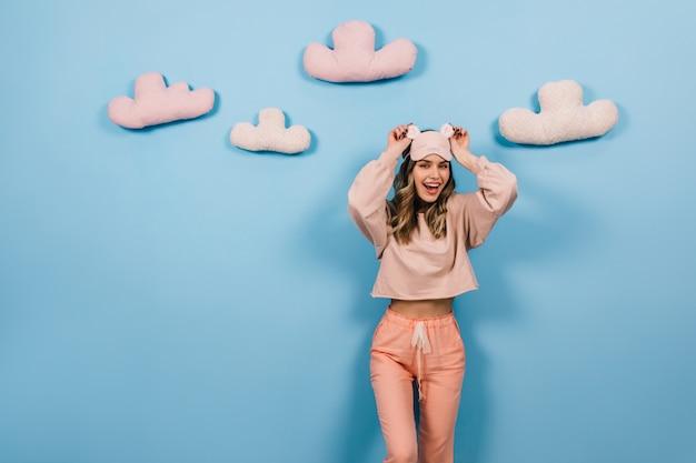 Femme extatique en pyjama rose s'amuser sur le mur bleu