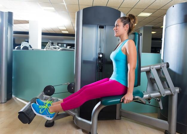 Femme d'extension de mollet à la machine d'exercice de gym