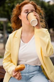 Femme à l'extérieur appréciant un beignet savoureux et une tasse de café
