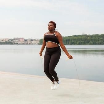 Femme à l'extérieur corde à sauter