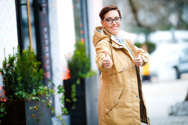 Femme à l'extérieur dans un imperméable et des lunettes dans les rues