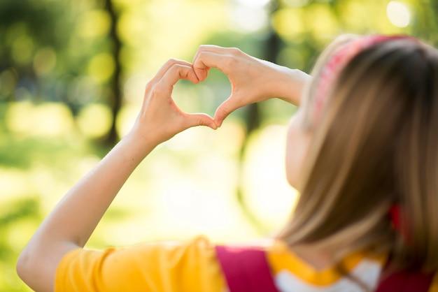 Femme à l'extérieur faisant un coeur avec les mains