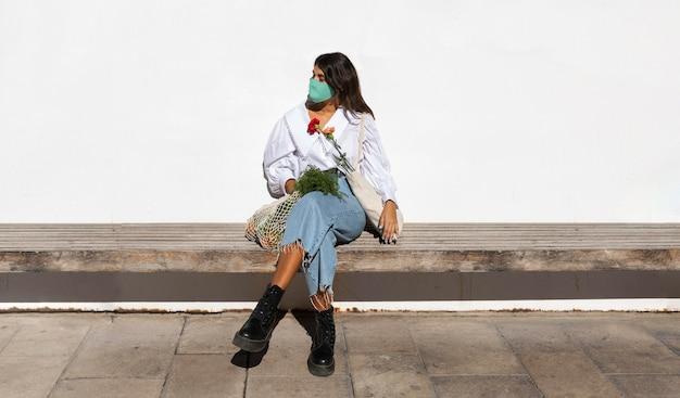 Femme à l'extérieur avec des fleurs et des sacs d'épicerie