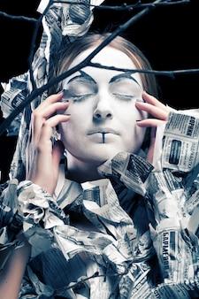 Femme extravagante avec des nouvelles de papier habillé. visage créatif, côté obscur.