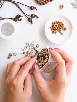 Femme fabriquant des accessoires avec des pièces métalliques