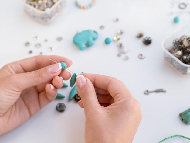 Femme fabriquant des accessoires avec des pierres turquoises