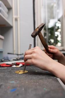 Femme fabriquant dans un morceau de métal doré