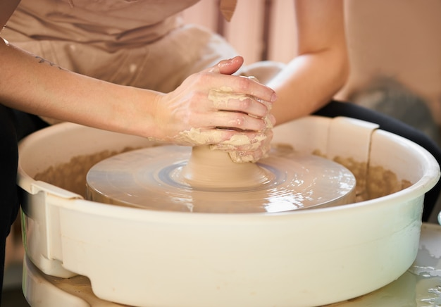Femme fabriquant des poteries en céramique sur roues, création d'objets en céramique.
