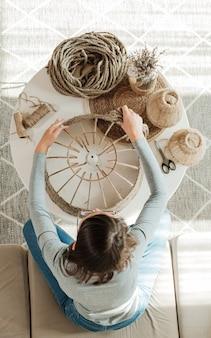Une femme fabrique une lampe de bricolage à la main à partir de corde de jute, vue de dessus