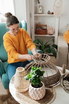 Une femme fabrique une lampe de bricolage à la main à partir de corde de jute