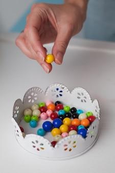 La femme fabrique un ornement à partir de perles.
