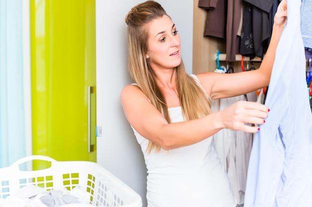 Femme en face de la garde-robe dans la chambre à coucher du linge propre pliant