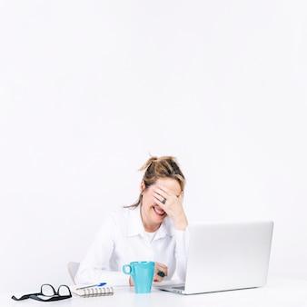 Femme facepalming sur lieu de travail