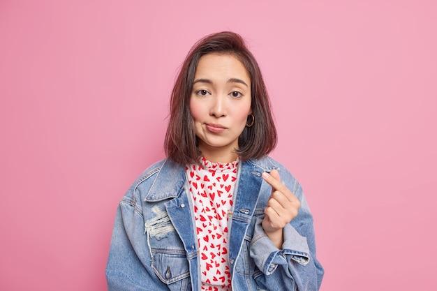 Une femme façonne un geste coréen comme symbole de l'amour montre un mini coeur exprime des sentiments véridiques porte une veste en jean