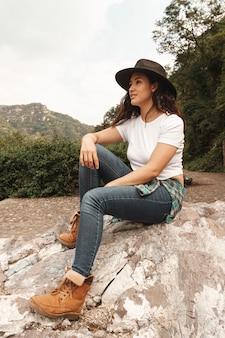 Femme faible angle avec chapeau dans nature