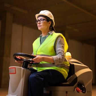 Femme de faible angle conduisant une machine de nettoyage