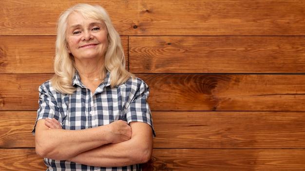 Femme faible angle avec un mur en bois comme toile de fond