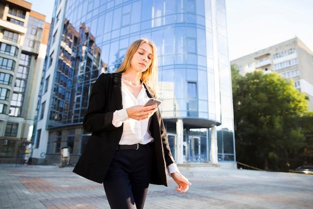 Femme à faible angle s'éloignant du bâtiment
