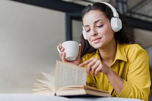 Femme faible angle avec une tasse et des écouteurs