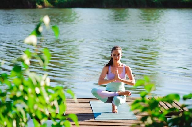 Femme faire du yoga en plein air. femme exerçant vital et méditation pour club de style de vie fitness à la nature